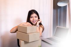 Young asian owner business woman working at home for online shopping,using labtop and packaging product. Young asian owner business woman working at home for Stock Photo