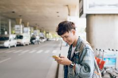 Young asian passenger waiting for taxi at the airport with phone Stock Images