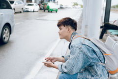 Young asian passenger waiting for taxi at the airport. With phone Royalty Free Stock Image