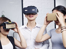 Young asian people trying virtual reality goggles. Three young asian people wearing different types of virtual reality (VR) goggles Stock Images