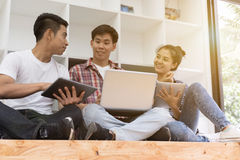 Young asian people are using different gadgets and smiling, sitt Royalty Free Stock Photo