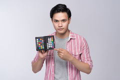 Young asian photographer holding color checker card, while working in studio stock photography