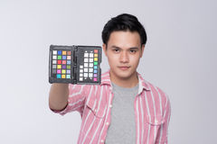 Young asian photographer holding color checker card, while working in studio stock images