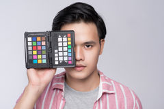 Young asian photographer holding color checker card, while working in studio stock photos