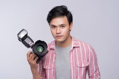 Free Young Asian Photographer Holding Digital Camera, While Working I Stock Photography - 100561962