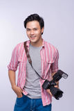 Young asian photographer holding digital camera, while working i Royalty Free Stock Image