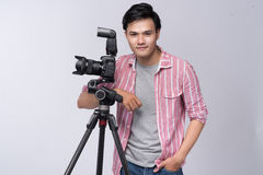 Young asian photographer holding digital camera, while working i Stock Photography