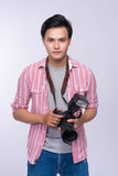 Young asian photographer holding digital camera, while working i Royalty Free Stock Photo