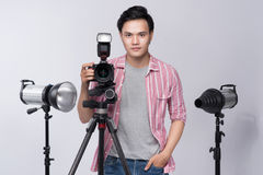 Young asian photographer holding digital camera, while working i Stock Images