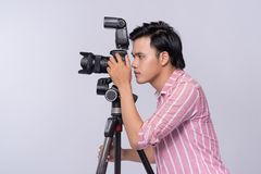 Young asian photographer holding digital camera, while working i Royalty Free Stock Photography