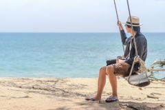 Young Asian photographer man on swing at the beach. Young Asian photographer man on wooden swing at the beach, male traveler relaxing with seascape in summer Royalty Free Stock Photography