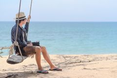 Young Asian photographer man on swing at the beach. Young Asian photographer man on wooden swing at the beach, male traveler relaxing with seascape in summer Stock Photos