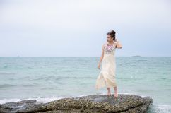 Young asian portrait standing on stone. Sea stock photography