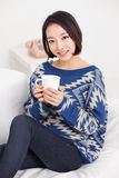 Young Asian pretty woman having a cup of coffee. Royalty Free Stock Photography