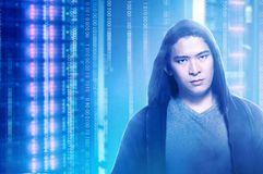Young asian programmer man in black hoodie standing. With digital binary code background stock photos