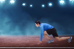 Young asian runner man kneeling ready in start position. On race track Stock Photos
