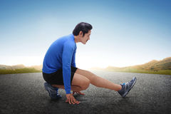 Young asian runner stretching his legs after running exercise. At outdoor Stock Photography