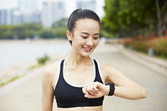 Young asian runner with wearable device royalty free stock images