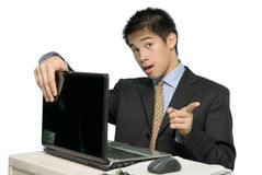 Young Asian salesman at laptop. Young Asian dynamic businessman or salesman in formal attire sitting behind a laptop PC and pointing convincingly with his finger Stock Photos