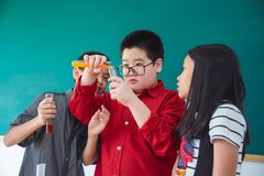 School children doing chemistry experiment. Young asian school children doing chemistry experiment in classroom royalty free stock photo