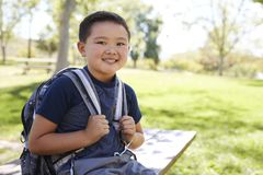 Young Asian schoolboy with backpack smiling to camera royalty free stock photography