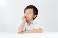 Young Asian schoolboy daydreaming Stock Image