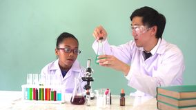 Young scientist holding a flask and teaching African American mixed kid in chemistry lab experiment. Young Asian scientist holding glass tube flask and teaching stock video footage