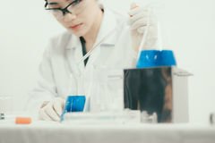 Young Asian scientist working in the lavatory with test tubes and other equipment Stock Images