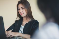 Young Asian secretary female working with laptop Stock Photos