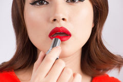 Young asian sexy woman with dark hair using red lipstick.  Royalty Free Stock Image