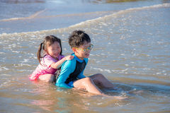 Siblings laughing happily after being hit by the sea Royalty Free Stock Images