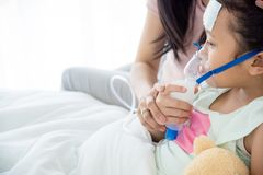 Sick girl sitting on bed with oxygen mask. Young asian sick girl sitting on bed with oxygen mask royalty free stock image