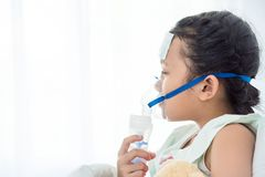 Sick girl sitting on bed with oxygen mask. Young asian sick girl sitting on bed with oxygen mask royalty free stock photography