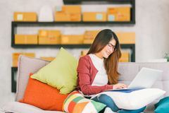 Young Asian small business owner working on laptop computer at home. Online marketing packaging and delivery scene, startup SME entrepreneur or freelance woman stock photo