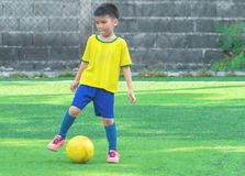 Young soccer player with yellow ball on training field. Young Asian soccer player with yellow ball on training field stock photography