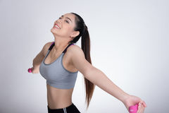 Young asian sporting woman training with dumbbell. Pretty athletic girl making physical exercise against white background. Health royalty free stock photography