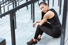 Young asian sportswoman sitting on stadium stairs and looking at camera. Attractive young asian sportswoman sitting on stadium stairs and looking at camera Royalty Free Stock Photography