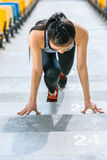 Young asian sportswoman in starting position on stadium stairs. Fitness woman running concept Royalty Free Stock Images