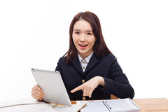 Young Asian student girl using tablet PC. On the desk isolated on white background Stock Photos