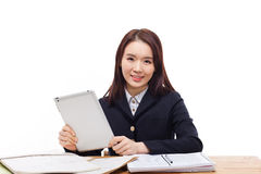 Young Asian student girl using tablet PC. On the desk isolated on white background Stock Photography