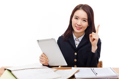 Young Asian student girl using tablet PC. On the desk isolated on white background Royalty Free Stock Images