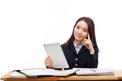 Young Asian student girl using tablet PC. On the desk isolated on white background Royalty Free Stock Photo