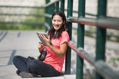 Young Asian student in her outdoor activity, holding a tablet pc Royalty Free Stock Photos