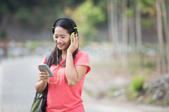 Young Asian student in her outdoor activity, listening to the music Royalty Free Stock Photo