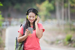 Young Asian student in her outdoor activity, listening to the music Royalty Free Stock Image