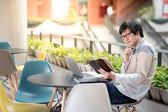 Young Asian student man reading book in college building Royalty Free Stock Photo