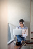 Young Asian student man using laptop in college. Young Asian man with glasses and headphones using laptop computer and listening to music during self-learning Royalty Free Stock Photography