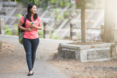 Young Asian student outdoor walking while holding her book Royalty Free Stock Photography