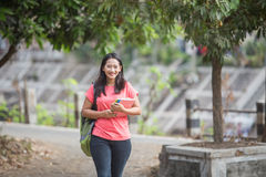 Young Asian student outdoor walking while holding her book Stock Photos