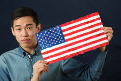 Young Asian student showing US national flag and looking at came Stock Photography